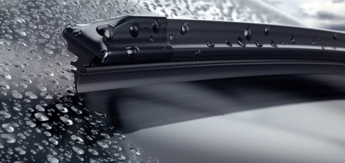 Car,Windshield,With,Rain,Drops,And,Frameless,Wiper,Blade,Closeup.